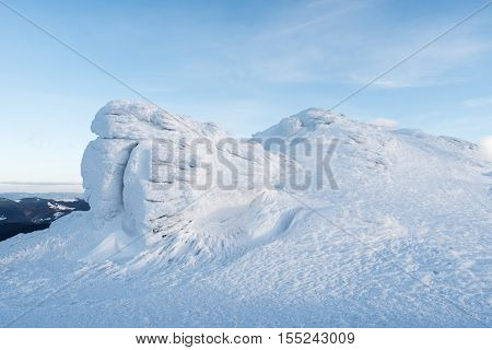 Winter landscape with rocks in the mountains. Beautiful snow and neve on the stones. The light of th