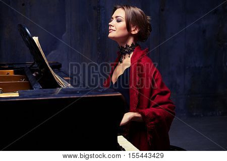 Side mid shot of cheerful young woman with stylish make-up and hair bun enjoys playing the piano. En