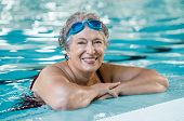 Mature woman wearing swim goggles at swimming pool. Fit active senior woman enjoying retirement  in  poster