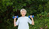 Постер, плакат: Зрелая женщина делает ее упражнения в саду