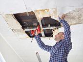 Man Repairing Collapsed Ceiling poster