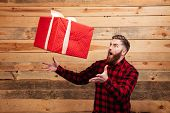 Young bearded man trying to catch gift box in motion isolated on wooden background poster