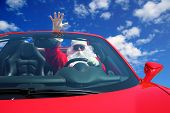 Santa Claus. Santa Drives fast in his Red Sports Car with a Blue Sky and fluffy white clouds. Santa  poster