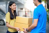 Young Asian Girl Receiving Parcel From Delivery Man, Delivery Man Brings Delivering Parcel Box. Fast poster