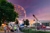 Attraction Ferris Wheel On Summer Evening In City Amusement Park. poster