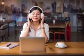 Beautiful Asian Woman Relaxing And Listening To Music In Cafe With Laptop Computer And Coffee Cup. P poster