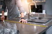 Young Asian Man Using Tape Measure For Measuring Granite Countertops On Modern Kitchen Counter In Sh poster