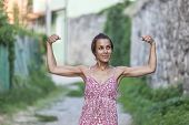 The Girl Shows Her Muscles. A Woman In A Summer Dress Shows Her Biceps. Strong Brunette. Slender Gir poster