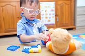 Cute Little Asian 2 Years Old Toddler Baby Boy Child Playing Doctor With Plush Toy At Home, Kid Hold poster