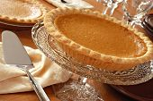 Elegant still life of pumpkin pie on antique pedestal plate with pie server and dinnerware.  Closeup