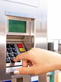 picture of dial pad  - Woman entering PIN on a ticket vending machine - JPG