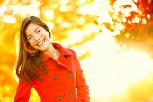 Autumn fashion girl wearing red trench coat in sun flare foliage. Fall woman portrait of happy lovel