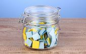 Pieces of paper for lottery in jar on wooden table on blue background