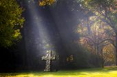 pic of flood-lights  - Sunlit cross stands on a lawn of a cemetery - JPG