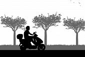 A silhouette of a man on motorcycle who drives along the road in spring