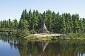 stock photo of tipi  - Traditional Native American tipi on a lake shore - JPG