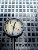 image of square mile  - Iconic clock face in front of Canary Wharf tower - JPG