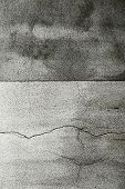 stock photo of stippling  - Cracked grungy cement wall background with a stippled rough surface and a central division line between a lighter and darker grey colour - JPG