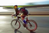image of triathlon  - Athlet riding bicycle at sunny day on coastal road blurred motion - JPG