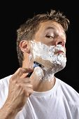stock photo of shaving  - Handsome Caucasian man with shaving cream contorts face as he shaves his neck with black background - JPG