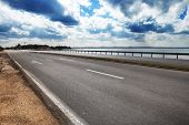 stock photo of tree lined street  - road by the sea on a sunny day - JPG