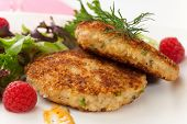stock photo of crab-cakes  - Two crab cakes appetizer garnished with spicy sauce green salad and raspbery - JPG