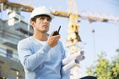 stock photo of headgear  - Male architect with blueprints using walkie - JPG