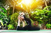 image of raja  - Yoga Raja Kapotasana pigeon pose by woman in black costume in the garden with palms banana trees and plants in the pots - JPG