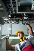 picture of heavy equipment operator  - Electrician in a safety hat and headphones on a factory - JPG