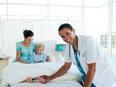 stock photo of hospital patient  - Little girl staying in a hospital as a patient with her doctor and her mother - JPG