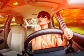 stock photo of dangerous situation  - Women make up lips at the wheel the car - JPG