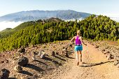 stock photo of canary-islands  - Young woman cross country running in mountains on sunny summer day - JPG