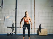 stock photo of snatch  - Fit and attractive caucasian female holding a barbell in her hands. Crossfit woman lifting heavy weights in gym.