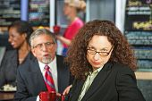 pic of disrespect  - Man bothering frustrated business woman in coffee house - JPG