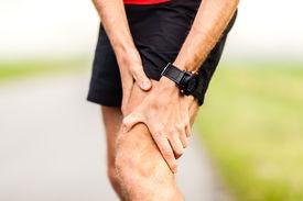 stock photo of crossed legs  - Runner holding sore leg knee pain from running or exercising jogging injury or cramp cross country in summer nature - JPG