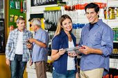 image of hardware  - Portrait of happy couple holding tool set in hardware store with customers in background - JPG