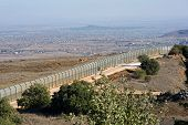 stock photo of golan-heights  - The fence of the border between Israel and Syria as seen from a hill on the Golan Heights about 10 kilometers south - JPG