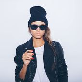 stock photo of tobacco smoke  - Hipster girl in sunglasses and black leather jacket smoking cigar - JPG
