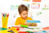 stock photo of scissors  - Cute small boy crafting with scissors, paper and glue sitting at the table with drawings on background