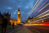 image of westminster bridge  - A bus speeding past tourists admiring Big ben and Houses of Parliament on Westminster Bridge in London England - JPG
