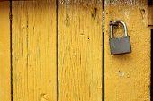 picture of oxidation  - old metallic padlock on yellow wooden door interesting textured view - JPG