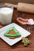 foto of cookie  - Several gingerbread Christmas cookies on a white plate with cookie cutters a rolling pin and several cookies in the background. ** Note: Soft Focus at 100%, best at smaller sizes - JPG