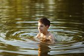 stock photo of debonair  - Happy smiling boy having fun swimming in the water - JPG
