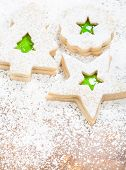 stock photo of linzer  - Christmas linzer cookies decorated with powdered sugar and with green jam center - JPG