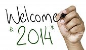 stock photo of reveillon  - Welcome 2014 hand writing with a black mark on a transparent board - JPG