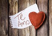 stock photo of miss you  - Te Amo written on a peace of paper and a heart on a wooden background - JPG