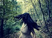 picture of drama  - Scared young woman running through a forest at night looking back - JPG