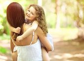 stock photo of children walking  - Joyful child and mother having fun friendly family walks outdoors - JPG