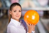 stock photo of bowling ball  - Beautiful young woman in a bowling alley is smiling and holding bowling ball - JPG