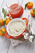 stock photo of mandarin orange  - Porridge in an orange bowl juice and mandarins on the table - JPG